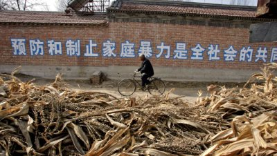 A man cycles past a wall painted with an anti-domestic violence slogan in the rural province of Hebei in Northern China. (AP Photo/Elizabeth Dalziel)