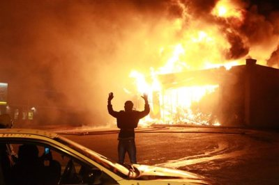 """In this Nov. 24, 2014 photo, a protestor poses for a """"hands up"""" photo in front of a burning building on West Florissant Ave. in Ferguson, Mo. 'Hands Up, Don't Shoot' has become a rallying cry despite questions whether Michael Brown's hands were raised in surrender before being fatally shot by a Ferguson police officer. (AP Photo/St. Louis Post-Dispatch, Christian Gooden, File)"""