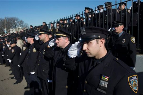 Police officers salute as the hearse of New York city police officer Rafael Ramos drives along his funeral procession route in the Glendale section of Queens, Saturday, Dec. 27, 2014, in New York. Ramos and his partner, officer Wenjian Liu, were killed Dec. 20 as they sat in their patrol car on a Brooklyn street. The shooter, Ismaaiyl Brinsley, later killed himself. (AP Photo/John Minchillo)