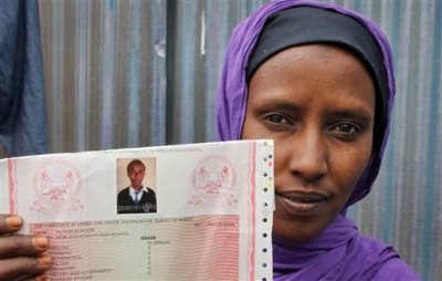 In this July 21, 2014 photo, Habiba Abdikadir Mohammed displays a photo of her brother Aliyow Alinoor, who was killed in a police shooting incident in Nairobi, Kenya. The shooting in the Mukuru slum, recounted to The Associated Press by Alinoor's friend Adan Hussein, is a recent example of how Kenya's Western-supported police force has turned even ordinary cops on the beat into killers, doling out death to terror suspects, shakedown victims, even children. (AP Photo/Khalil Senosi)