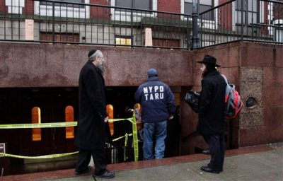 Members of the Lubavitch community watch a police officer enter Chabad-Lubavitch Hasidic headquarters, Tuesday, Dec. 9, 2014, in New York.  A knife-wielding man stabbed an Israeli student inside the Brooklyn synagogue before being fatally shot by police after he refused to drop the knife. The student, Levi Rosenblatt, is in stable condition. (AP Photo/Mark Lennihan)