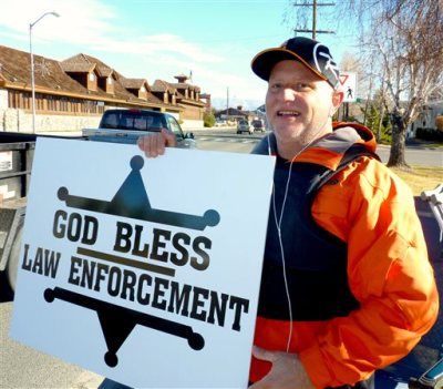 """In this Dec. 22, 2014 photo, passing motorists honk as retired Douglas County sheriff's deputy John Munk of Gardnerville, Nev., holds a sign showing his support for law enforcement, in front of the Minden Post Office south of Carson City. """"It's disheartening how people are treating law enforcement across the country,'' said Munk, who retired in 2012 after more than 20 years on the force. (AP Photo/The Record Courier, Kurt Hildebrand)"""