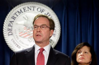 Michigan Attorney General Bill Schuette speaks after U.S. Attorney Carmen Ortiz, right, announced indictments of 14 owners and employees from the New England Compounding Center Wednesday, Dec. 17, 2014, in Boston. More than 750 people in 20 states were sickened, and 64 died after they contracted fungal meningitis and other illnesses in 2012 from tainted steroids made by the Framingham, Mass., company. The 265 Michigan cases included 19 deaths. (AP Photo/Steven Senne)