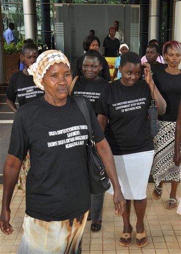 """In this photo taken Tuesday, June 5, 2012, Ugandan women walk out of the Constitutional Court disappointed after losing a case against the government over maternal deaths during childbirth, prior to taking the issue further to the Supreme Court, in the capital Kampala, Uganda. More than 100 women die during childbirth each week in Uganda, a heartbreaking statistic that has energized activists to go to the Supreme Court in a bid to force the government to put more resources toward maternal health care to prevent the wave of deaths. Writing on t-shirts in English and Swahili reads """"Not another needless death: Government stop deaths of mothers now"""". (AP Photo/Stephen Wandera)"""