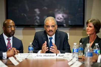 U.S. Attorney General Eric Holder, center, sits next to Rev. Raphael G. Warnock, pastor of Ebenezer Baptist Church, left, and U.S. Attorney Sally Quillian Yates, right, while meeting with law enforcement and community leaders for a roundtable discussion at Ebenezer Baptist Church, Monday, Dec. 1, 2014, in Atlanta. President Barack Obama instructed Holder to set up regional meetings on building trust between law enforcement and the communities they serve in the wake of clashes between protesters and police in Ferguson, Missouri. The Atlanta event Monday is the first one. (AP Photo/David Goldman)