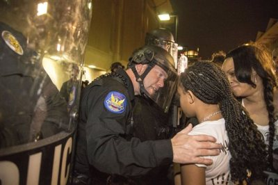 """In this Monday, Dec. 8, 2014 photo, a Phoenix police officer in riot gear talks with Aiyana Rains, 9, the daughter of Rumain Brisbon, as she participates with hundreds of protesters headed towards police headquarters to demand transparency in the case that left her father dead following a confrontation with a police officer on Dec. 2. Grasping her hand, the officer said, """"I'm sorry."""" (AP Photo/The Arizona Republic, Nick Oza)"""