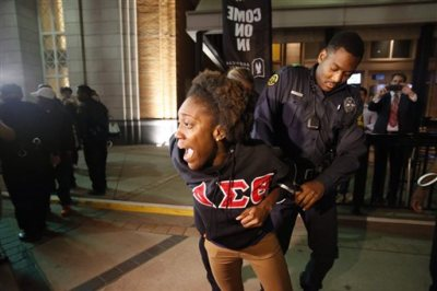 In this photo taken on Dec. 5, 2014, a protestor is restrained and taken into custody as she marched with others against police brutality near the American Airlines Arena in downtown Dallas. The protest was in response to a New York City grand jury not prosecuting a police officer in the death of Eric Garner. Delta Sigma Theta and Alpha Kappa Alpha sororities recently advised members that if they join in the protests, they should not wear any identifying clothing. AKA would later reverse course on its directive. (AP Photo/The Dallas Morning News, Vernon Bryant)