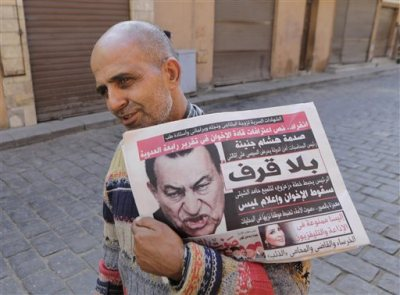 """An Egyptian man carries newspapers with a photo of former Egyptian President Hosni Mubarak on it, in Cairo, Egypt, Monday, Dec. 1, 2014. A judge dismissed murder charges Saturday, Nov. 29, against former President Hosni Mubarak and acquitted his security chief over the killing of protesters during Egypt's 2011 uprising, crushing any hope of a judicial reckoning on behalf of the hundreds victims of the revolt that toppled him. Protests are planned for Tuesday against the verdict. The headline on the newspaper in Arabic reads, """"enough already."""" (AP Photo/Amr Nabil)"""