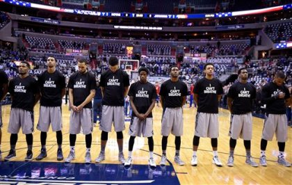 "Members of the Georgetown basketball team stand for the National Anthem wearing ""I Can't Breathe"" t-shirts before an NCAA college basketball game against Kansas, Wednesday, Dec. 10, 2014, in Washington. (AP Photo/Nick Wass)"
