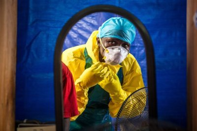 In this Thursday, Oct. 16, 2014 file photo, a healthcare worker dons protective gear before entering an Ebola treatment center in the west of Freetown, Sierra Leone.  Dr. Brima Kargbo, Sierra Leone's chief medical officer, confirmed Thursday Dec. 18, 2014, that Dr. Victor Willoughby died earlier in the day after being tested positive for Ebola on Saturday, the 11th doctor in the country to die from the disease that is ravaging West Africa. (AP Photo/Michael Duff, FILE)