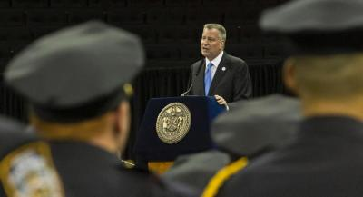 New York City Mayor Bill de Blasio, center, address Police Academy graduates during their graduation ceremony, Monday June 30,2014 at Madison Square Garden in New York.  The New York Police Department swore in 600 new officers after a weekend of violence across the city, where at least 21 people were shot and four were killed. Many will partner with veteran officers and sent out to target the most violent, crime-ridden neighborhoods. (AP Photo/Bebeto Matthews)
