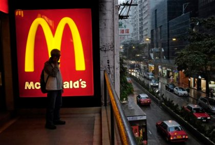 In this April 2, 2014, file photo, a man talks on a mobile phone next to a downtown McDonald's in Hong Kong. McDonald's says a key global sales figure fell 2.2 percent in November 2014 as U.S. sales continue to soften and it contends with ongoing difficulties from a food-safety scandal in China. (AP Photo/Vincent Yu, File)