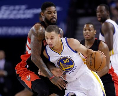 Golden State Warriors' Stephen Curry (30) is defended by Toronto Raptors' Amir Johnson during the first half of an NBA basketball game Friday, Jan. 2, 2015, in Oakland, Calif. (AP Photo/Marcio Jose Sanchez)