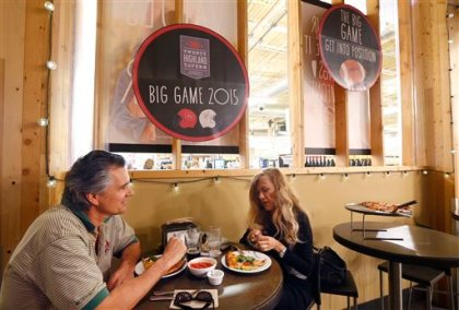 """So as not to infringe on the NFL Super Bowl name trademark, all non-rights holders have to use different wording to promote any Super Bowl activity like this Whole Foods grocery store where diners enjoy a meal near promotional signs for """"the big game"""" Wednesday, Jan. 28, 2015, in Phoenix. (AP Photo/Ross D. Franklin)"""