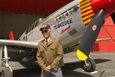 """This April 7, 2011 photo by Bruce Talamon shows Clarence E. """"Buddy"""" Huntley Jr., a member of the Tuskegee Airmen, the famed all-black squadron that flew in World War II, posing with a P-51C Mustang fighter plane similar to the one that he was a crew chief on while overseas during the war, at Torrance, Calif., Airport. Huntley and fellow Tuskegee Airman Joseph Shambrey, lifelong friends who enlisted together, both died on the same day, Monday, Jan. 5, 2015, in their Los Angeles homes, relatives said Sunday, Jan. 11, 2015. Both were 91. Huntley and Shambrey enlisted in 1942 and were shipped overseas to Italy in 1944 with the 100th Fighter Squadron of the Army Air Force's 332nd Fighter Group. As mechanics, they kept the combat planes flying. (AP Photo/Bruce Talamon (c) 2011 All Rights Reserved)"""