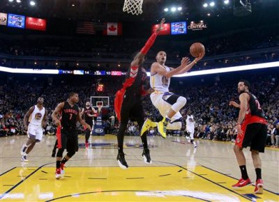 Golden State Warriors' Stephen Curry goes in for a shot as Toronto Raptors' Terrence Ross (31) defends during the first half of an NBA basketball game Friday, Jan. 2, 2015, in Oakland, Calif. (AP Photo/Marcio Jose Sanchez)