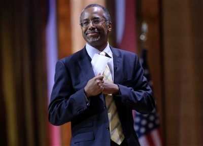 "In this March 8, 2014 file photo, Dr. Ben Carson, professor emeritus at Johns Hopkins School of Medicine, puts his notes back in his pocket after speaking at the Conservative Political Action Committee annual conference in National Harbor, Md. Carson's publisher will review allegations that the conservative activist failed to properly credit sources in his 2012 book ""America the Beautiful."" The allegations were raised by a BuzzFeed article that listed numerous examples of passages in Carson's book that closely resemble material which first appeared elsewhere. The book was co-written by Carson's wife, Candy Carson. (AP Photo/Susan Walsh, File)"