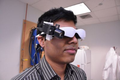 Biomedical engineering doctoral student Suman Mondal demonstrates the goggle prototype that uses infrared light to illuminate cancer cells (Wiley Price/St. Louis American)