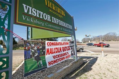 The sign for the city of Vicksburg, Miss., visitor's center shares space with a newer sign touting Super Bowl hero and New England Patriots cornerback Malcolm Butler as a hometown hero, Wednesday, Feb. 18, 2015. The city is holding a parade in Butler's honor on Saturday, Feb. 21. (AP Photo/Rogelio V. Solis)