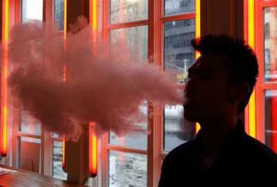 In this Feb. 20, 2014, File photo, a patron exhales vapor from an e-cigarette at the Henley Vaporium in New York. The first peek at a major study of how Americans smoke suggests many use combinations of products, and often e-cigarettes are part of the mix. It's a preliminary finding, but it highlights some key questions as health officials assess electronic cigarettes. (AP Photo/Frank Franklin II, File)