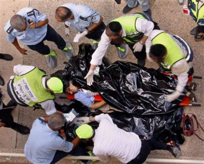 In this July 31, 2002 file photo. police and volunteers examine the body of one of the victims of an explosion at Hebrew University of Jerusalem. Palestinian officials are nervously watching a landmark terrorism trial in the U.S brought by victims of Palestinian suicide bombings and shootings aimed at civilians, fearing a negative verdict could hurt their international image at a time when they are preparing to press war crimes charges against Israel. (AP Photo/John McConnico, File)