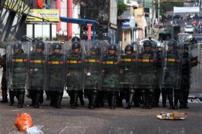 Bolivarian National Guard soldiers advances on demonstrators attacking a police station during an anti-government protest in San Cristobal, Venezuela, Tuesday, Feb. 24, 2015. Demonstrators protest after a 14-year-old boy died Tuesday after being shot in the head during an anti-government protest in Venezuela's restive western region. Preliminary investigations suggest the student was injured during a confrontation between police and protesters in the city, and died on the way to the hospital, according to San Cristobal Human Rights Commission President Jose Vicente Garcia. (AP Photo/STR)
