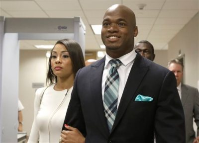 In this  Nov. 4, 2014, file photo, Minnesota Vikings running back Adrian Peterson leaves the courthouse with his wife Ashley Brown Peterson in Conroe, Texas. A federal judge has cleared the way for Peterson to be reinstated. U.S. District Judge David Doty issued his order Thursday, Feb. 26, 2015, less than three weeks after hearing oral arguments. (AP Photo/Pat Sullivan, File)