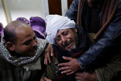 A man is comforted by others as he mourns over Egyptian Coptic Christians who were captured in Libya and killed by militants affiliated with the Islamic State group, outside of the Virgin Mary church in the village of el-Aour, near Minya, 220 kilometers (135 miles) south of Cairo, Egypt, Monday, Feb. 16, 2015. (AP Photo/Hassan Ammar)
