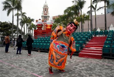 "A performer from Taiwan dressed as the ""Third Prince"" poses for a photograph in front of the sheep decorations during the rehearsal of International Chinese New Year Night Parade in Hong Kong Wednesday, Feb. 18, 2015. Decades ago the Chinese New Year holiday, also known as Spring Festival, had little impact outside of China. But as the country has gained outsized economic influence, the holiday, which has enormous cultural significance in the Chinese-speaking world, has become more prominent. (AP Photo/Kin Cheung)"