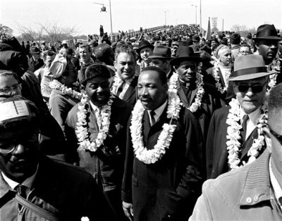 In this March 21, 1965 file photo, Martin Luther King, Jr. and his civil rights marchers cross the Edmund Pettus Bridge in Selma, Ala., heading for capitol, Montgomery, during a five day, 50 mile walk to protest voting laws. The Edmund Pettus Bridge gained instant immortality as a civil rights landmark when white police beat demonstrators marching for black voting rights 50 years ago this week in Selma, Alabama. What's less known is that the bridge is named for a reputed leader of the early Ku Klux Klan. Now, a student group wants to rename the bridge that will be the backdrop when President Barack Obama visits Selma on Saturday, March 7, 2015.  (AP Photo/File)