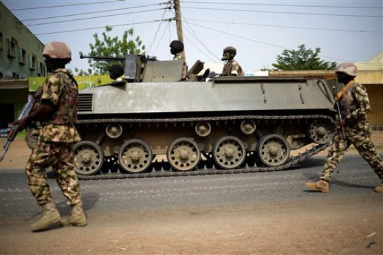 In this photo taken Monday March 9, 2015, Nigerian troops patrol in the north-eastern Nigeria city of Mubi, some 20 kms (14 miles) west of the Cameroon border. Nigerian troops recaptured Mubi from Boko Haram militants in February 2015. On Friday March 13, 2015, the Islamic State group's media arm Al-Furqan, in an audio recording by spokesman Abu Mohammed al-Adnani, said that Boko Haram's pledge of allegiance has been accepted, claiming the caliphate has now expanded to West Africa. (AP Photo/str)
