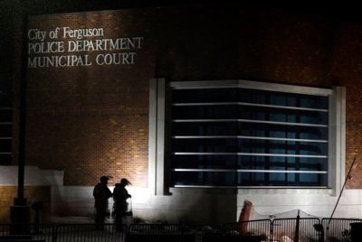 In this Nov. 26, 2014, file photo, nembers of Missouri National Guard stand outside of the Ferguson Police Department and the Municipal Court in Ferguson, Mo. A Justice Department investigation has found patterns of racial bias in the Ferguson police department and at the municipal jail and court. The full report, to be publicly released on March 4, says the investigation found Ferguson officers disproportionately used excessive force against blacks and too often charged them with petty offenses. (AP Photo/Jeff Roberson, File)