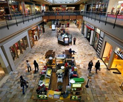 In this Nov. 28, 2014, file photo, shoppers look for deals inside the Flatiron Crossing Mall, a Macerich property in Broomfield, Colo. Mall operator Simon Property boosted its hostile bid for rival Macerich 5 percent. Simon said, Friday, March 20, 2015, it is willing to pay $95.50 per share for Macerich, or about $16.8 billion, up from its previous offer of $91 per share, or $16 billion. (AP Photo/Brennan Linsley, File)