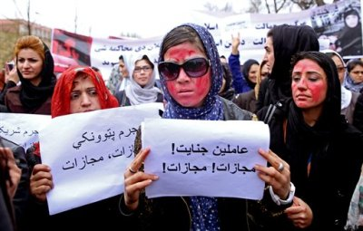 "Afghan women, demand justice for a woman who was beaten to death by a mob after being falsely accused of burning a Quran last week, during a protest in downtown Kabul, Afghanistan, Tuesday, March 24, 2015. Men and women of all ages carried banners bearing the bloodied face of Farkhunda, a 27-year-old religious scholar killed last week by a mob. Farkhunda, who went by one name like many Afghans, was beaten, run over with a car and burned before her body was thrown into the Kabul River. The poster at center with Persian writing reads, ""Farkhunda's murderers, execution."" (AP Photo/Massoud Hossaini)"