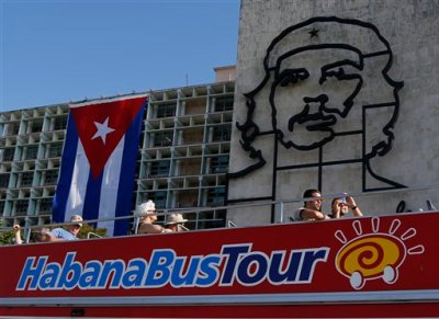 In this March 13, 2015 photo, tourists ride a double-decker bus backdropped by an iron sculpture of Cuban revolutionary hero Ernesto 'Che' Guevara on the facade of the Ministry of Interior in Revolution Square, in Havana, Cuba. Bookings to Cuba jumped 57 percent for one New York tour operator in the weeks after Washington said it would renew ties with Havana. In February, they were up 187 percent; and so far this month, nearly 250 percent.  (AP Photo/Desmond Boylan)