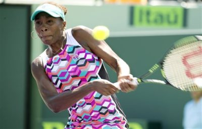 Venus Williams returns the ball to Caroline Wozniacki during their match at the Miami Open tennis tournament in Key Biscayne, Fla., Monday, March 30, 2015. (AP Photo/J Pat Carter)