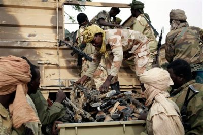 In this file photo taken on Wednesday March 18, 2015, Chadian soldiers collect weapons seized from Boko Haram fighters  in the Nigerian city of Damasak, Nigeria.  Hundreds of civilians, including many children, have been kidnapped and are being used as human shields by Boko Haram extremists, a top Nigerian official confirmed Wednesday, March 25, 2015. (AP Photo/Jerome Delay, File)