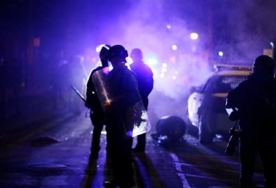 """In this Nov. 25, 2014 file photo, police officers watch protesters as smoke fills the streets in Ferguson, Mo. after a grand jury's decision in the fatal shooting of Michael Brown. Six months after 18-year-old Michael Brown died in the street in Ferguson, Missouri, the Justice Department is close to announcing its findings in the racially charged police shooting that launched """"hands up, don't shoot"""" protests across the nation. (AP Photo/Charlie Riedel, File)"""