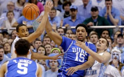 Duke's Jahlil Okafor (15) passes to Tyus Jones (5) as North Carolina's Brice Johnson, left, and Jackson Simmons defend during the first half of an NCAA college basketball game, Saturday, March 7, 2015, in Chapel Hill, N.C. (AP Photo/Gerry Broome)