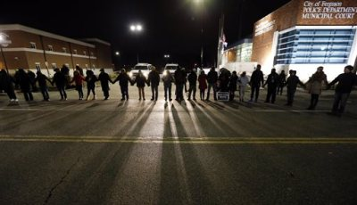 Protestors block traffic outside the Ferguson, Mo., police department, Wednesday, March 4, 2015, in Ferguson. The Justice Department on Wednesday cleared a white former Ferguson police officer in the fatal shooting of an unarmed black 18-year-old, but also issued a scathing report calling for sweeping changes in city law enforcement practices it called discriminatory and unconstitutional. (AP Photo/Charles Rex Arbogast)