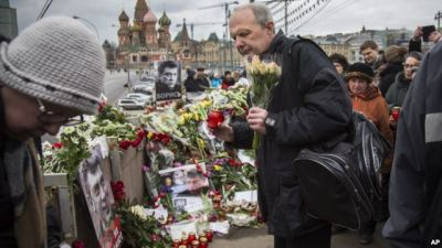 Mourners following the Russian tradition of memorializing a person nine days after a death lay flowers and votive candles at the place where Boris Nemtsov was gunned down near the Kremlin, in Moscow, on Saturday, March 7, 2015. (AP Photo)