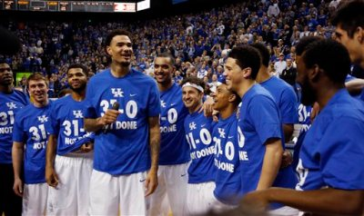 Kentucky's Willie Cauley-Stein, fourth from left, celebrates with teammates during a ceremony marking the teams undefeated regular season after an NCAA college basketball game, Saturday, March 7, 2015, in Lexington, Ky. Kentucky won 67-50. (AP Photo/James Crisp)