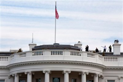 "Uniformed Secret Service agents patrol the top of the White House as seen from the South Lawn of the White House in Washington, Tuesday, March 17, 2015. According to the Secret Service a letter sent to the White House tentatively tested positive for cyanide. The letter was received at an off-site mail screening facility on March 16 and additional testing Tuesday returned a ""presumptive positive"" for cyanide. (AP Photo/Jacquelyn Martin)"