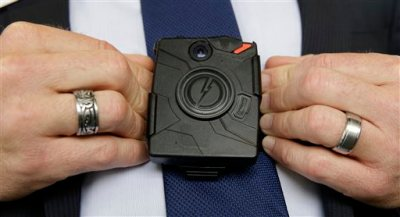 In this photo taken Thursday, Feb. 19, 2015, Steve Tuttle, vice president of communications for Taser International, demonstrates one of the company's body cameras for The Associated Press during a company-sponsored conference hosted by Taser at the California Highway Patrol Headquarters in Sacramento, Calif. Taser, the stun-gun maker, has become a leading supplier of body cameras for police and has cultivated financial ties to police chiefs whose departments have bought the recording devices.  A review by The Associated Press shows Taser is covering airfare and hotel stays for police chiefs who travel to speak at the company's marketing conferences. It is also hiring some recently retired chiefs as consultants, sometimes months after their cities signed contracts with Taser.(AP Photo/Rich Pedroncelli)