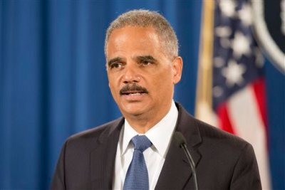 """In this Sept. 4, 2014, file photo, Attorney General Eric Holder speaks during a news conference at the Justice Department in Washington to announce the Justice Department's civil rights division will launch a broad civil rights investigation in the Ferguson, Mo., Police Department. City officials in Ferguson, Missouri, are pledging their full cooperation with a federal civil-rights investigation into their police department following the death of 18-year-old Michael Brown. Six months after 18-year-old Michael Brown died in the street in Ferguson, Missouri, the Justice Department is close to announcing its findings in the racially charged police shooting that launched """"hands up, don't shoot"""" protests across the nation. (AP Photo/Pablo Martinez Monsivais, File)"""