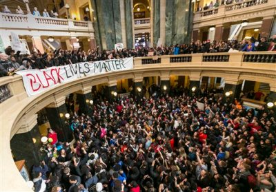 Demonstrators protest the shooting of Tony Robinson at the state Capitol Monday, March 9, 2015, in Madison, Wis. Robinson, 19, was fatally shot Friday night by a police officer who forced his way into an apartment after hearing a disturbance while responding to a call. Police say Robinson had attacked the officer. (AP Photo/Andy Manis)