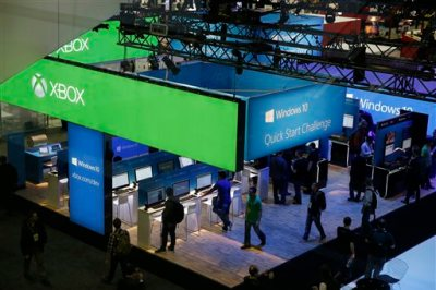 People walk through the Microsoft booth at the Game Developers Conference, Wednesday, March 4, 2015, in San Francisco. (AP Photo/Eric Risberg)