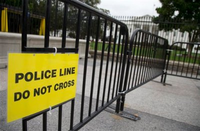 "In this Oct. 3, 2014, file photo, a temporary barrier marked with a sign ""Police Line Do Not Cross"" is seen along Pennsylvania Avenue in front of the White House in Washington. The Secret Service has placed a high-ranking supervisor on administrative leave and suspended the supervisor's security clearance after what it calls ""allegations of misconduct and potential criminal activity."" (AP Photo/Carolyn Kaster, File)"