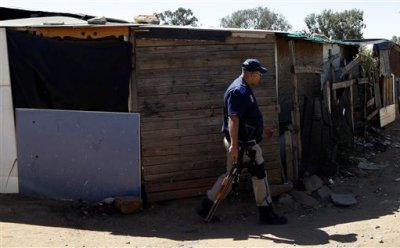 A police officer walks between the shacks in a informal settlement in Germiston, east Johannesburg, South Africa, Thursday, April 16, 2015. Fears of anti-immigrant attacks have escalated sending foreigners seeking refuge in camps and a police station. (AP Photo/Themba Hadebe)