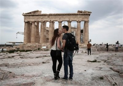 U.S. visitors Zach Branch, 19, right, and Madison Franklin, 18, both from California, kiss in front of the Parthenon during their visit at the Acropolis hill in Athens, on Wednesday, April 15, 2015. Vacations in Europe have a new attraction: the euro's steep drop in value is making the continent cheaper for tourists from across the world, especially the United States and China. Branch said that as a U.S. citizen is much cheaper to travel to Europe now, than it was two years ago. (AP Photo/Yorgos Karahalis)